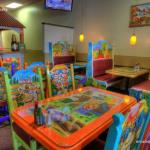 Colorful tabes and chairs with the bar in the background